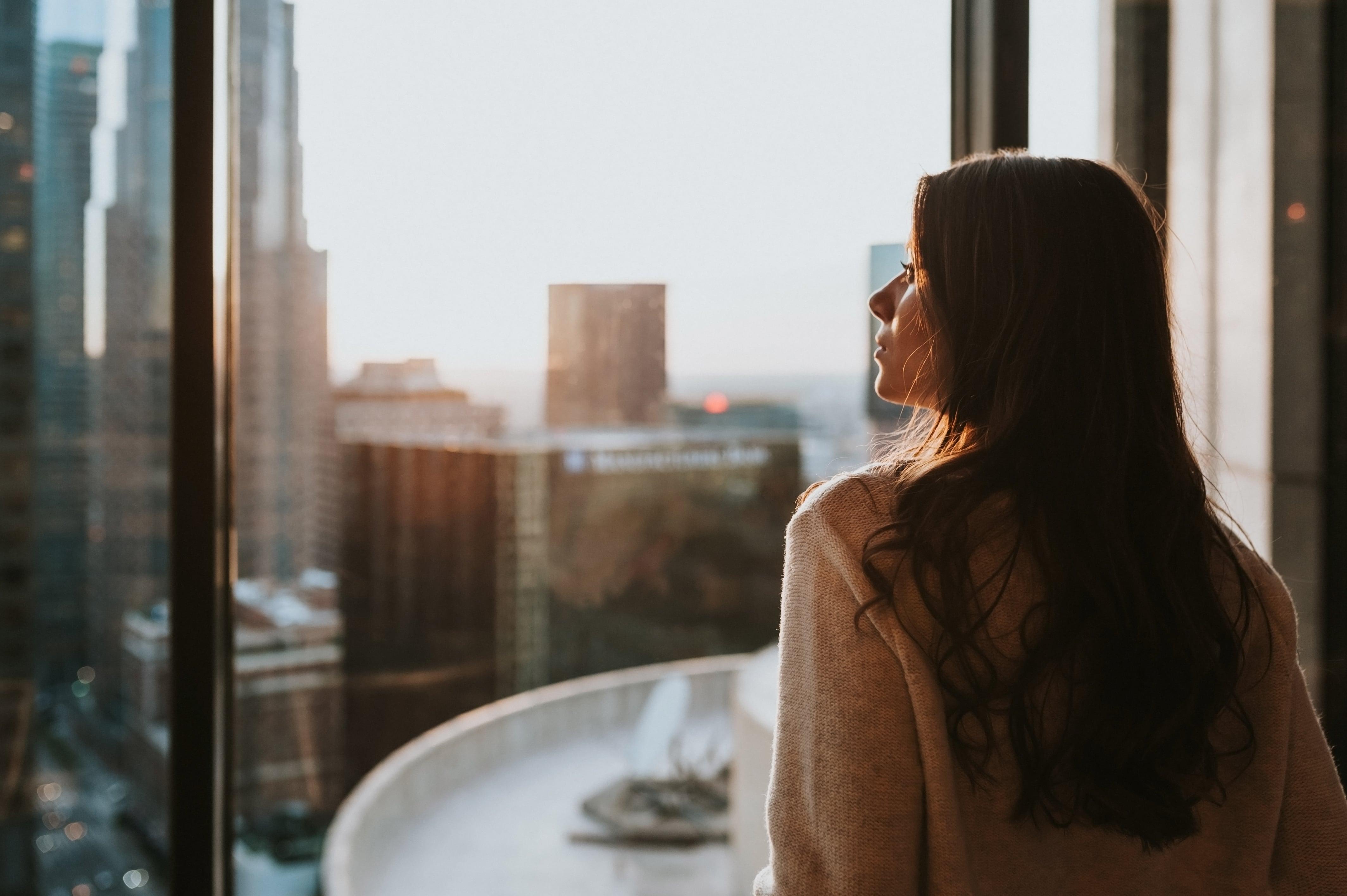 woman-staring-at-city-skyline-sunset-min
